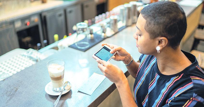 モバイルバンキングで小切手を預けるカフェの女性