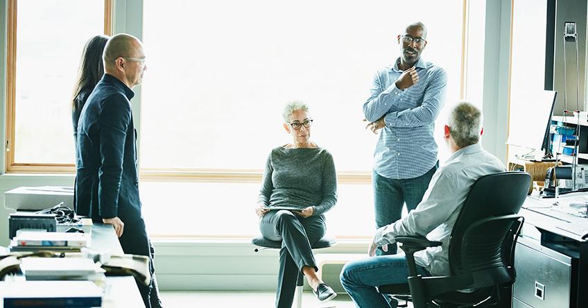 男性と女性の専門家のグループ、オフィスで立っている3人と椅子に座っている2人